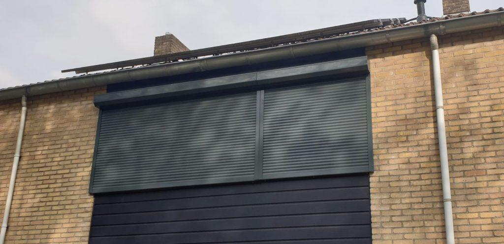 Gesloten rolluiken gemonteerd in de donker blauwe kleur van de woning | J. Meijering uit Opheusden, Gelderland