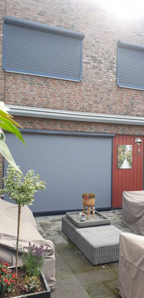 Antraciete rolluiken en screens aan de achterzijde van een woonhuis | Gemonteerd door J Meijering Montage uit Opheusden